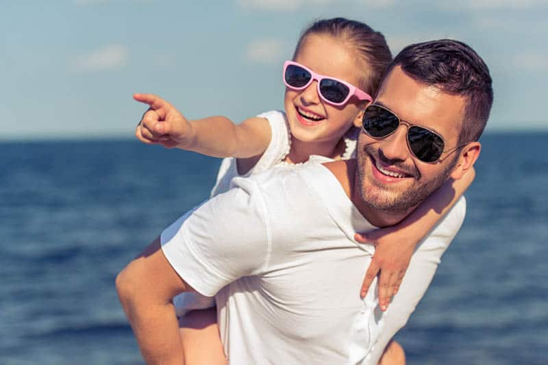 handsome father carrying his daughter on back wearing sunglasses both of them