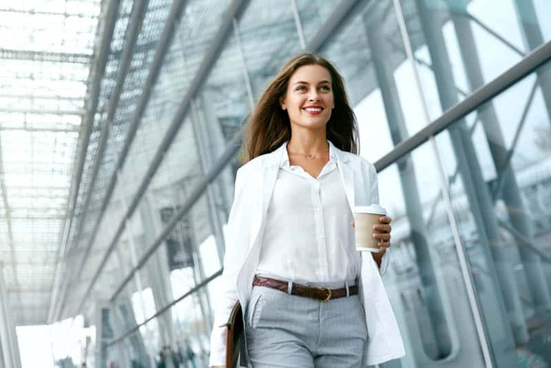 happy business woman holding cup of coffee while walking