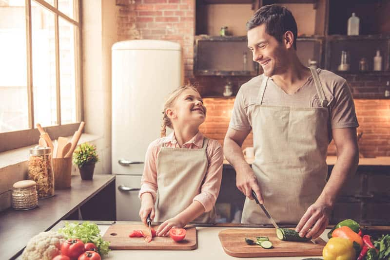 happy father and daughter cooking together in the kitchen