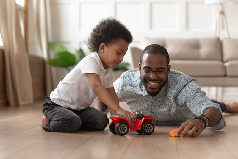 happy father playing with son on the floor with car toys