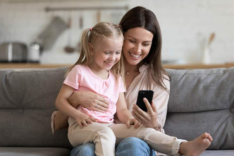 happy mother with cute daughter on the couch holding mobile phone