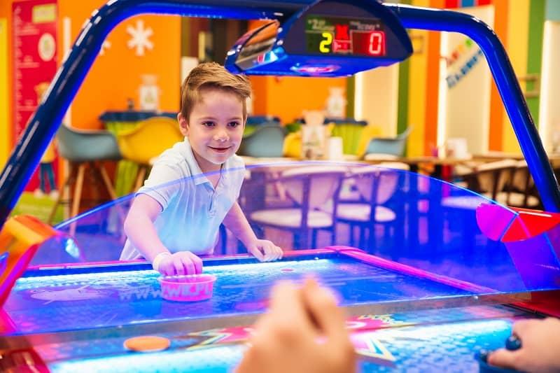 little boy playing air hockey at an arcade
