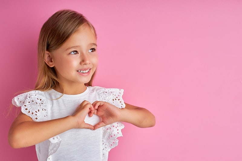 little girl making a heart shape with her hands while posing in front of a pink background