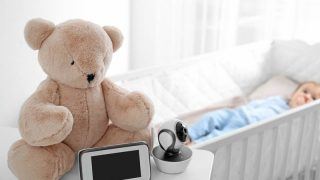 baby monitor with video screen next to a teddy bear and baby in crib