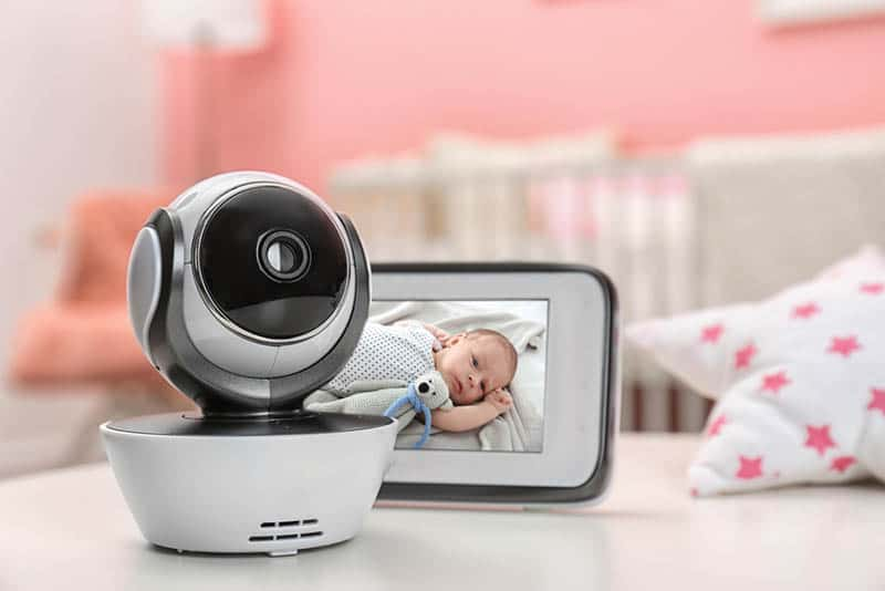 modern security camera with monitor with baby image on it on the table in bedroom