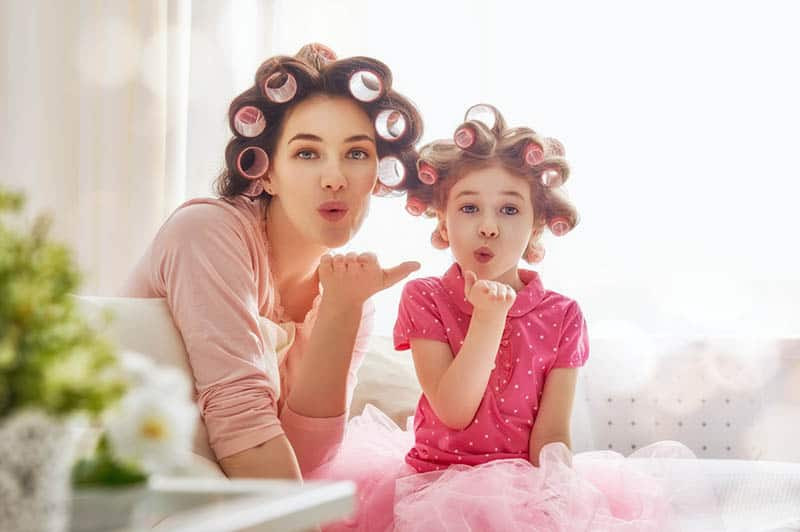 mother and daughter doing their hair in bedroom and sending kisses