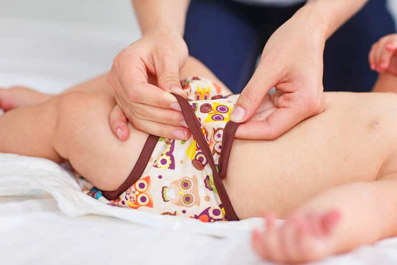 mother changing cloth diaper to her baby on the bed