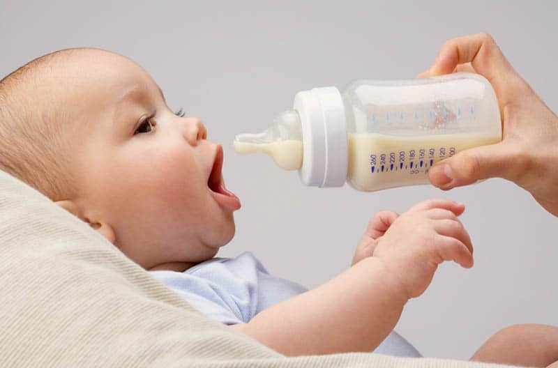 mother giving milk bottle to her baby at home