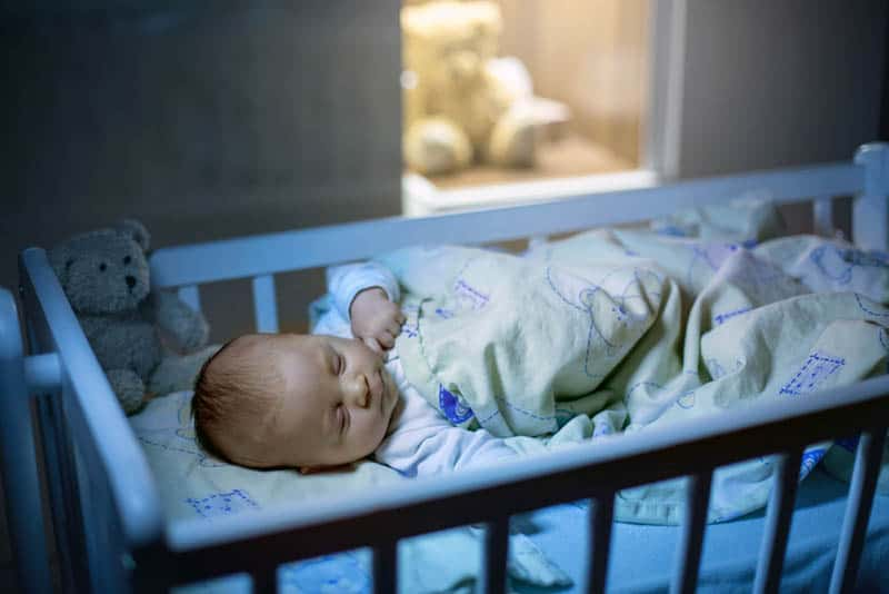 newborn baby sleeping in a crib covered with blanket at night