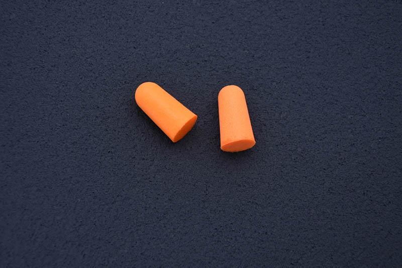 orange earplugs on dark table
