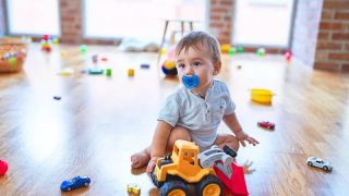 cute baby boy with pacifier sitting on the floor with toys