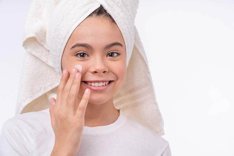 pretty smiling girl with hair in towel using face cream