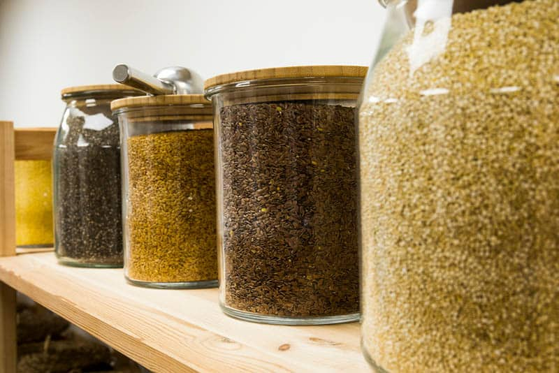 quinoa grains in big glass jars on the wooden table in store