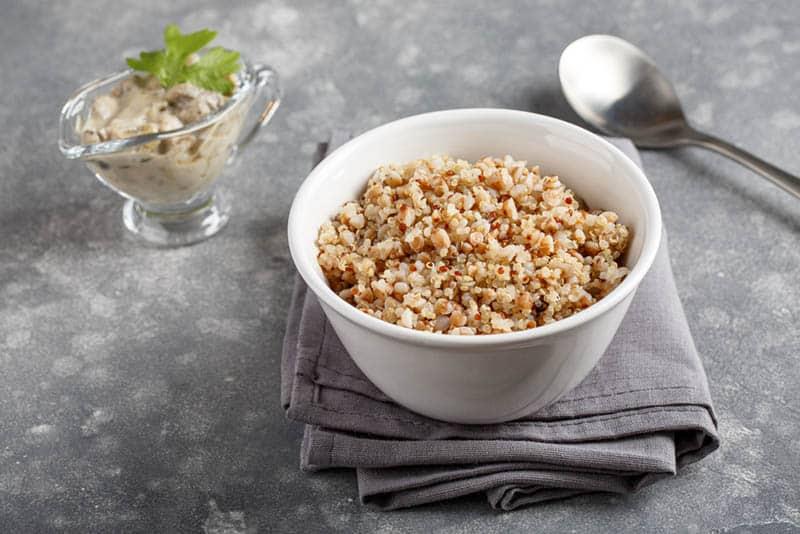 quinoa porridge in white bowl with spoon on the kitchen cloth