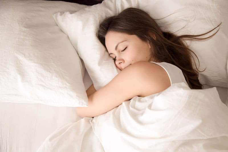 relaxed young woman sleeping on belly in the bed