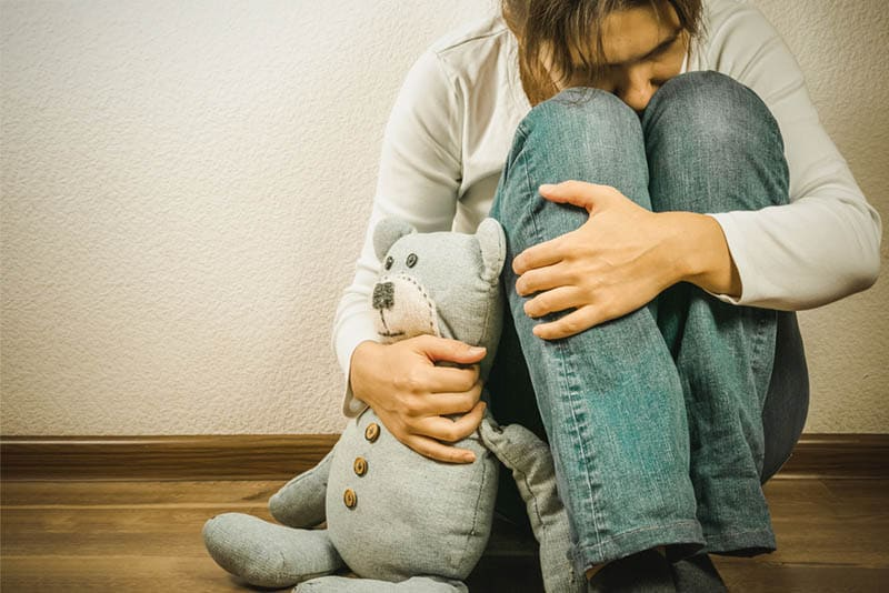 sad woman sitting on the floor and hugging a toy