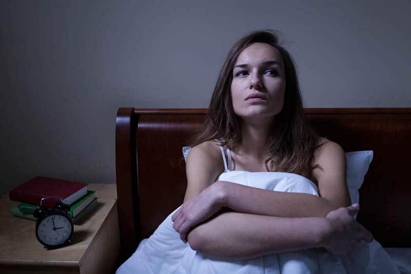 serious woman sitting in bed in deep thoughts