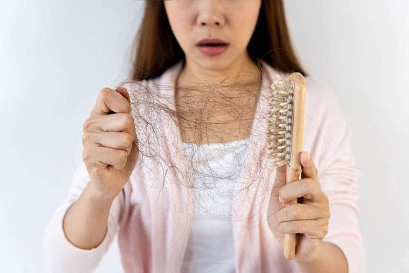 shocked pregnant woman looking at hair loss in her hand with brush
