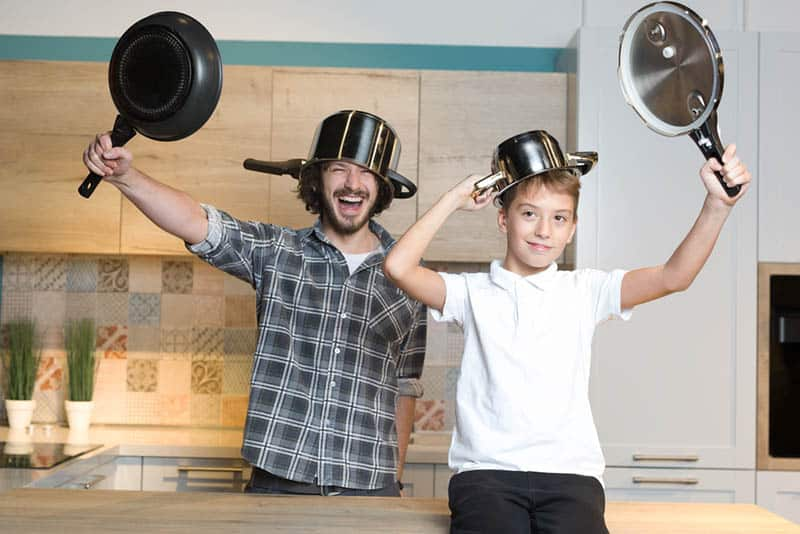 silly father and son playing with kitchen dishes at home