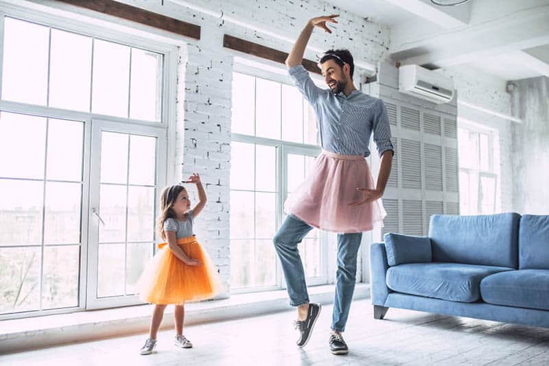 silly father dancing with his cute little daughter in skirts