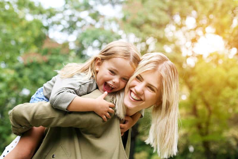 smiling blond mother carrying her daughter on back outdoor in the park