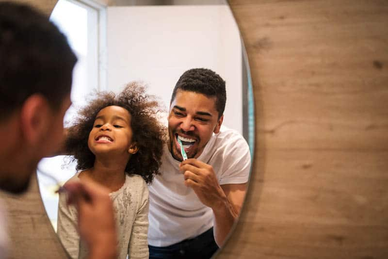 smiling father brushing his teeths with daughter in the bathroom