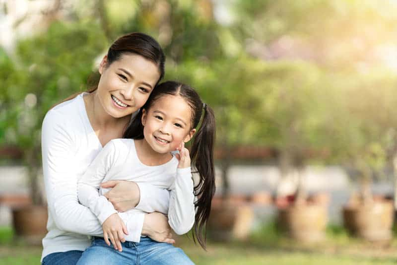 smiling mother hugging with daughter outdoor in public