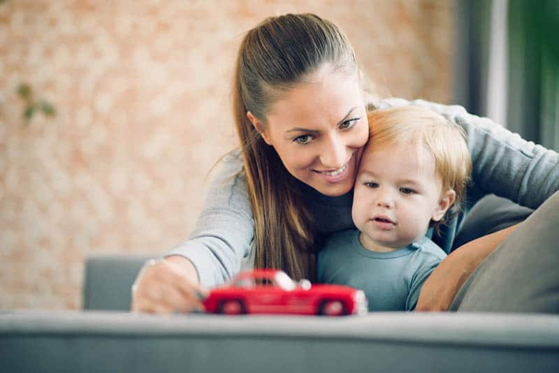 smiling mother playing with her son with red car toy at home