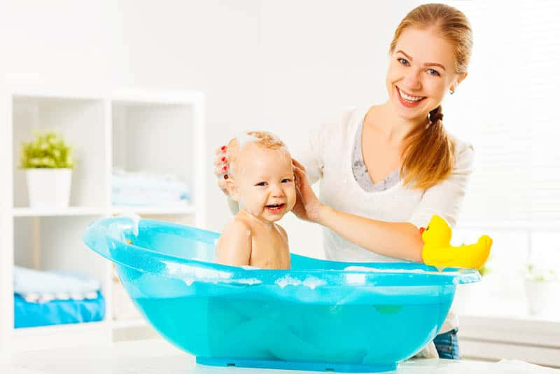 smiling mother posing with happy baby in bathtube at home