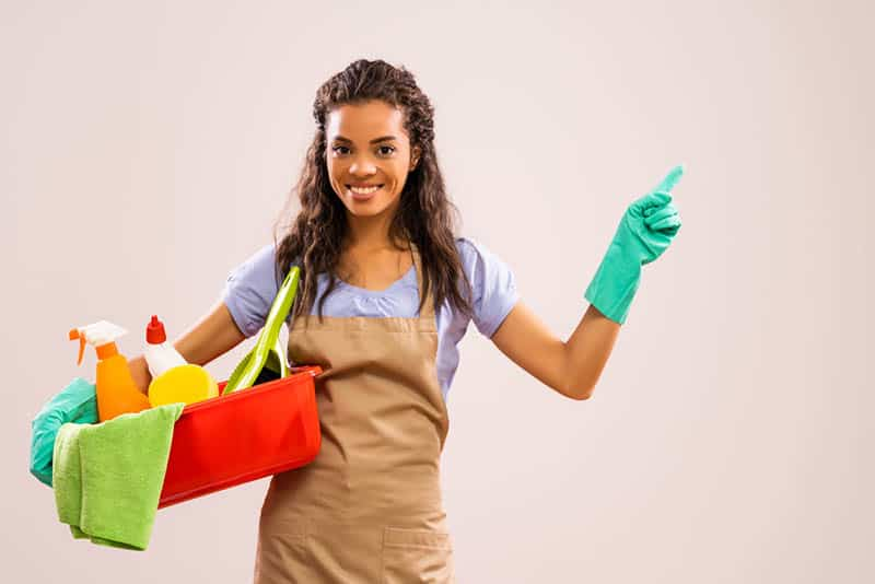 smiling young woman holding in hands cleaning products ready to clean