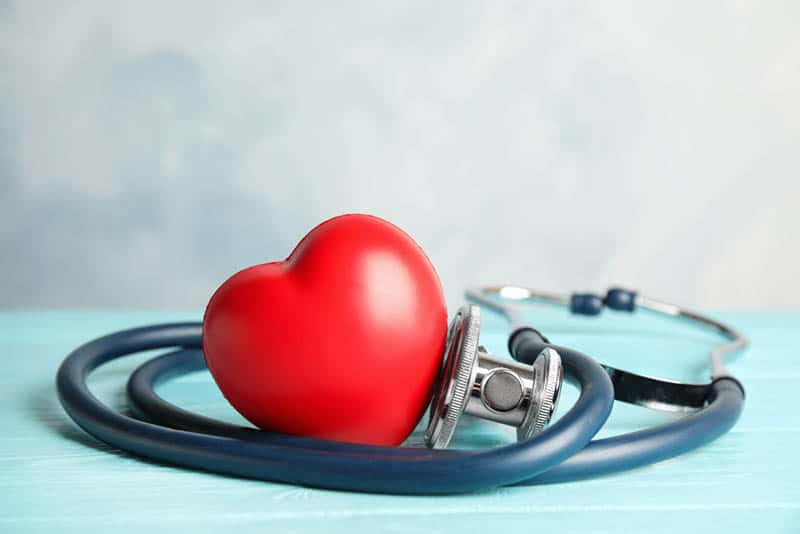 stethoscope and red heart on blue wooden table
