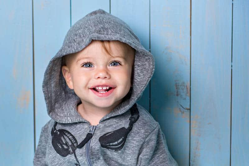 sweet baby boy wearing hoodie posing in front of blue wooden wall
