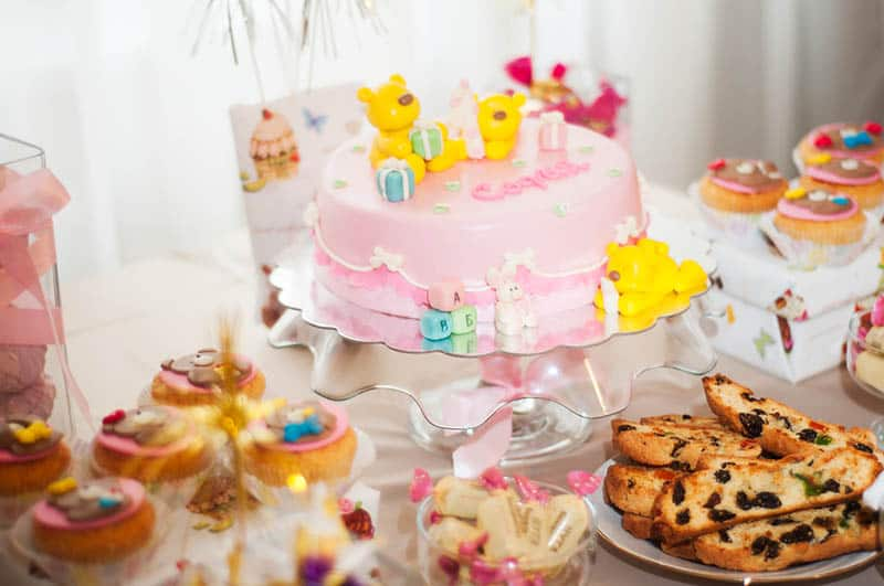 sweet cake for baby shower with other sweeties on the table