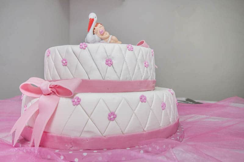 sweet pink cake for baby girls on the pink cloth on the table