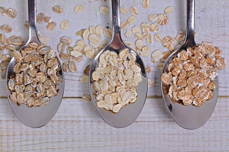 three kitchen spoons with whole grain oats on the wooden table