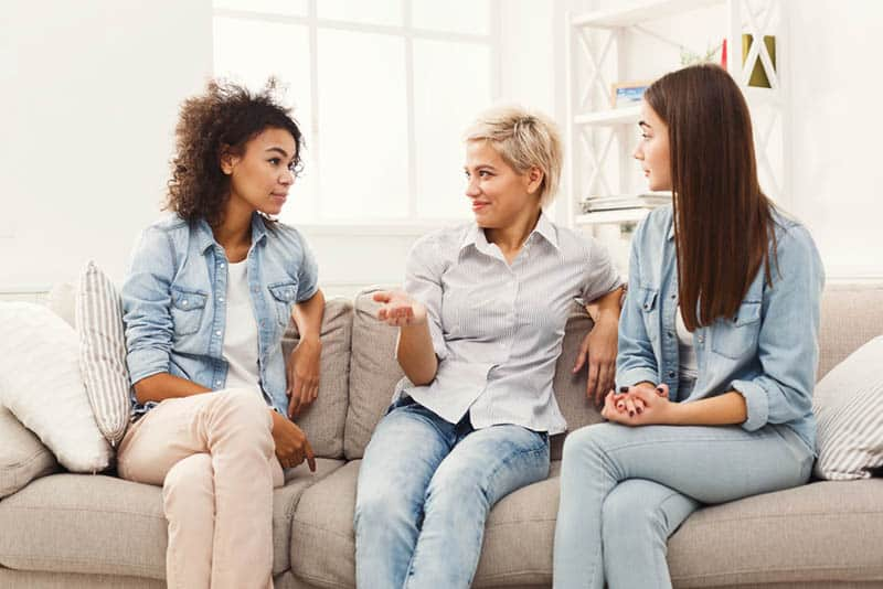 three young women talking on the couch at home