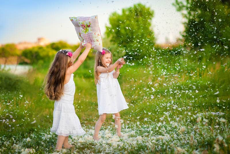 two girls playing with pillow plumage outdoor
