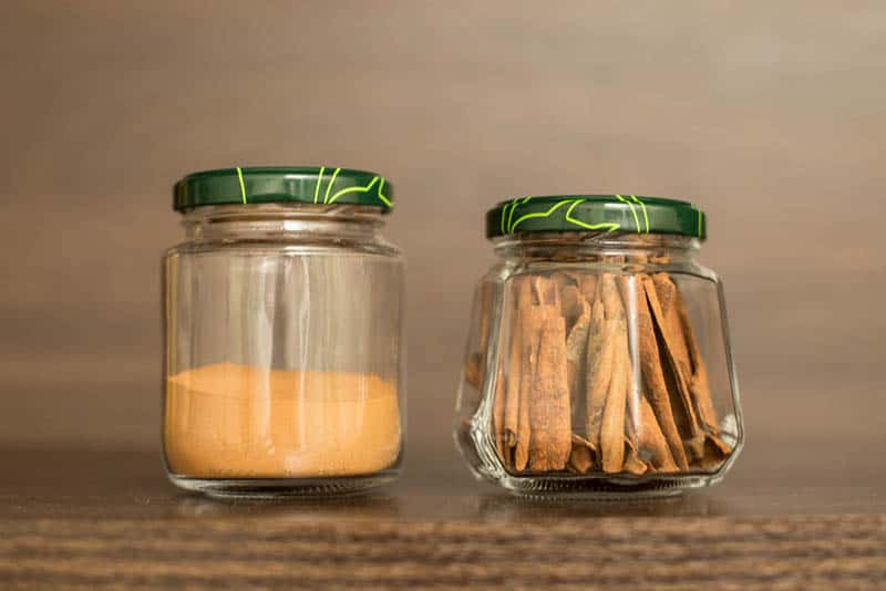 two jars of cinnamon in different types on the wooden table