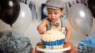 adorable baby boy eating his birthday cake