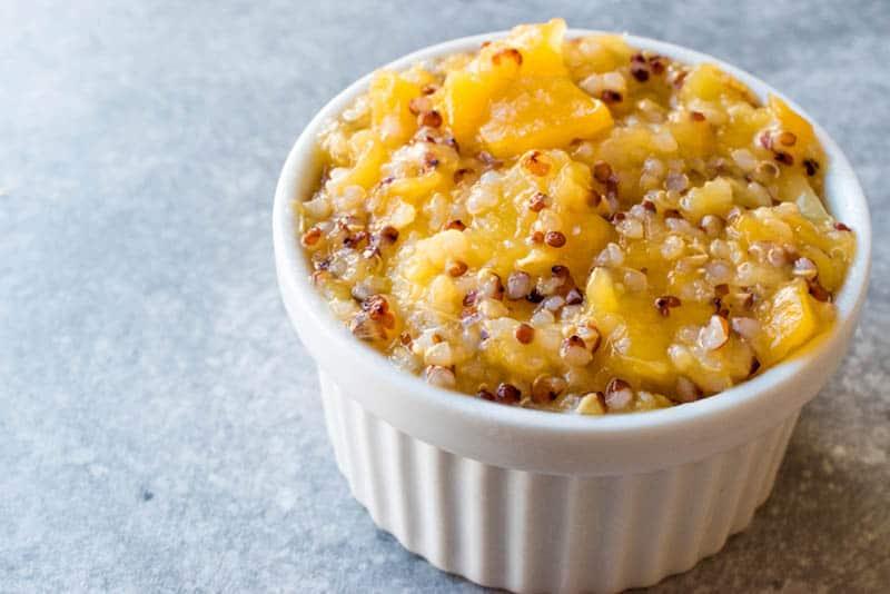 white acai bowl of quinoa and mango food on the table