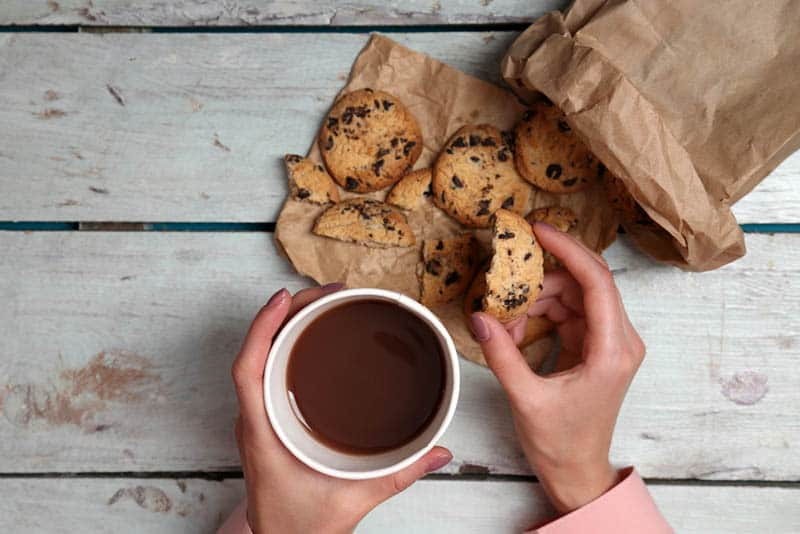 woman holding a cup of coffee and a bag full of cookies on the wooden table