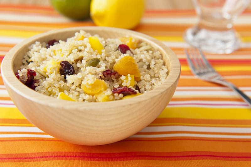 wooden bowl full of quinoa seeds and fruit on the colorful table