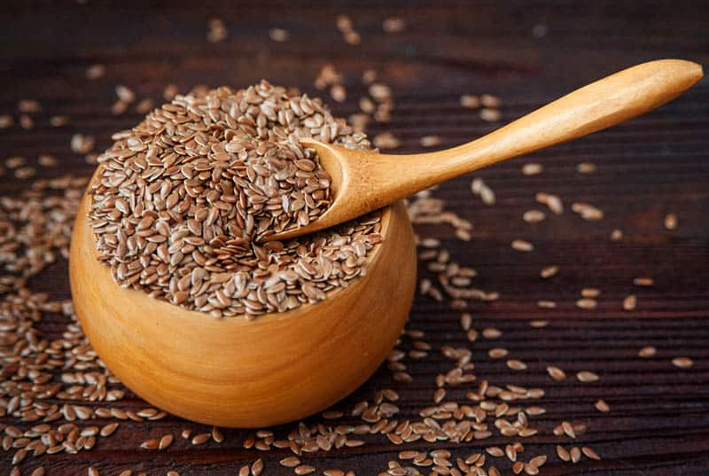wooden bowl of flax seeds with spoon on the table