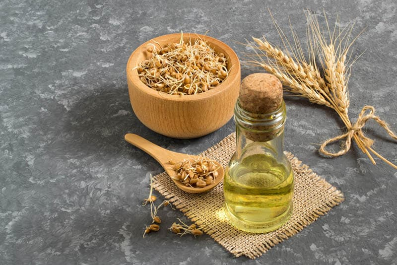 wooden bowl of wheat seeds with spoon and a bottle of germ oil on the grey table