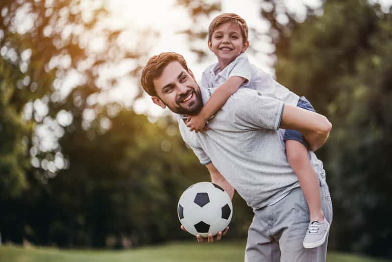 young father carrying his son on back and holding a footbal ball
