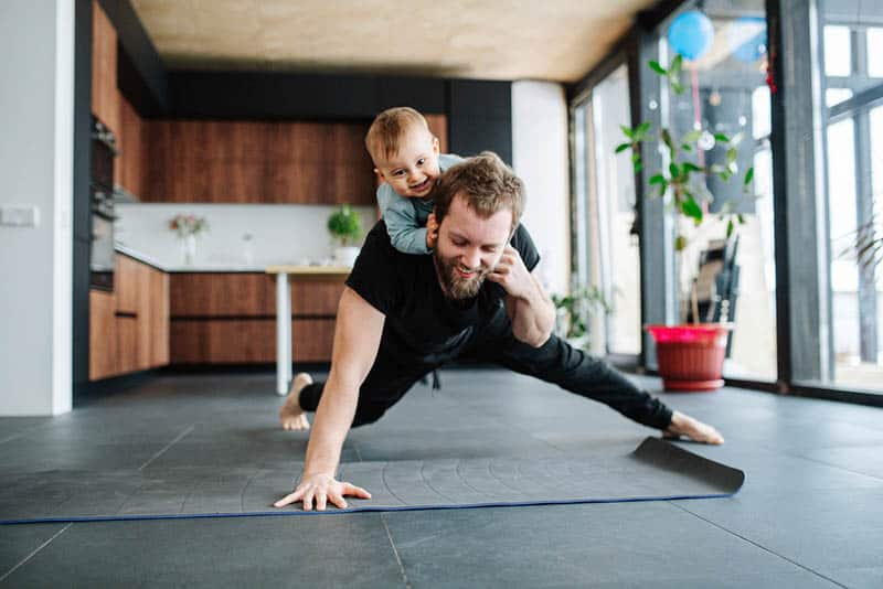 young father exercising at home while carrying his son on back