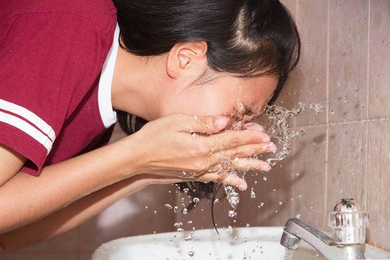 young girl washing her face in bathrooom basin