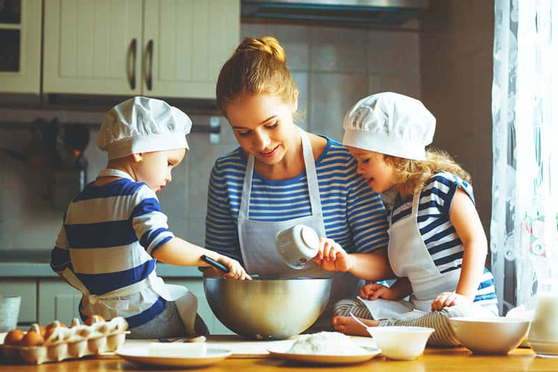young mother cooking together with her kids in the kitchen