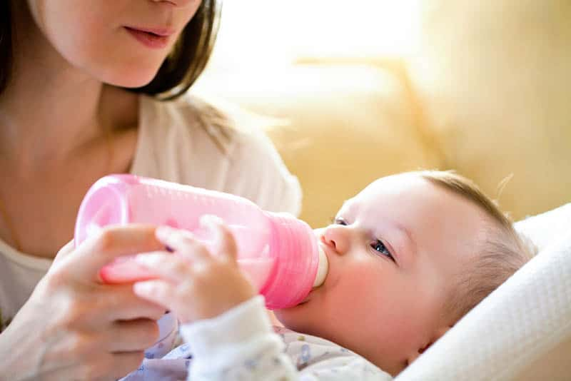 young mother feeding baby with pink milk bottle
