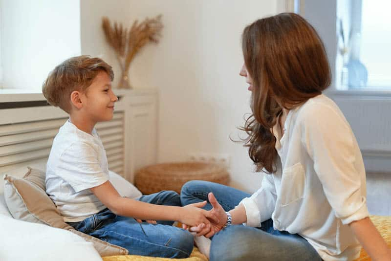 young mother holding son for hand while talking